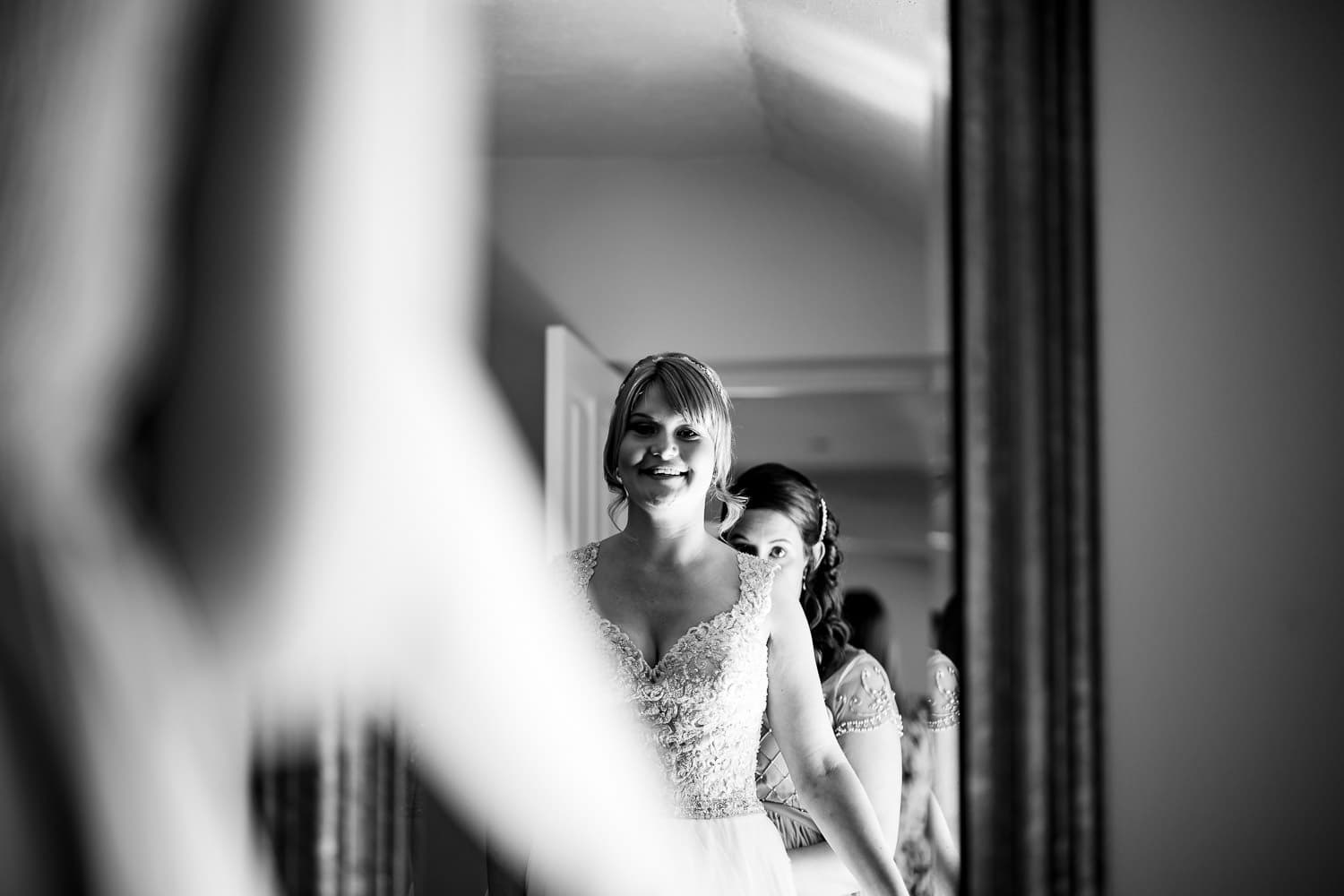 bride smiles as she herself in the mirror for the first time by Warwick House Wedding Photography