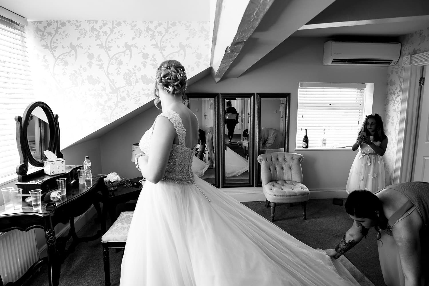 flower girl takes pictures of the bride on her mobile phone while the maid of honour fixes the brides dress