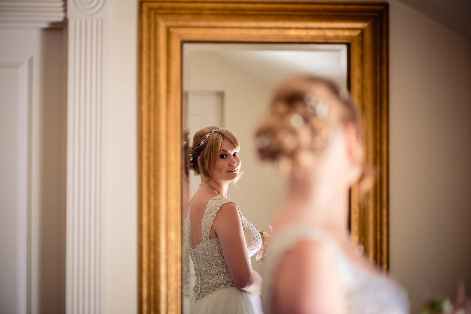 bride captured looking at herself in the mirror by Warwick House Wedding Photography