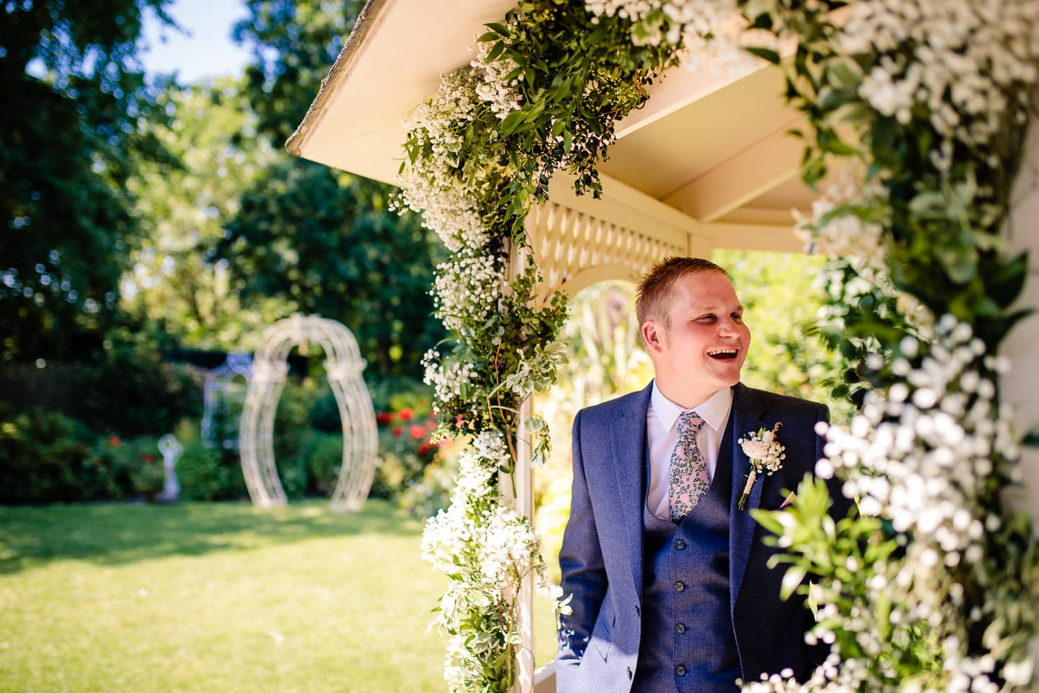 groom laughs and jokes with bestman before the ceremony by Warwick House Wedding Photography