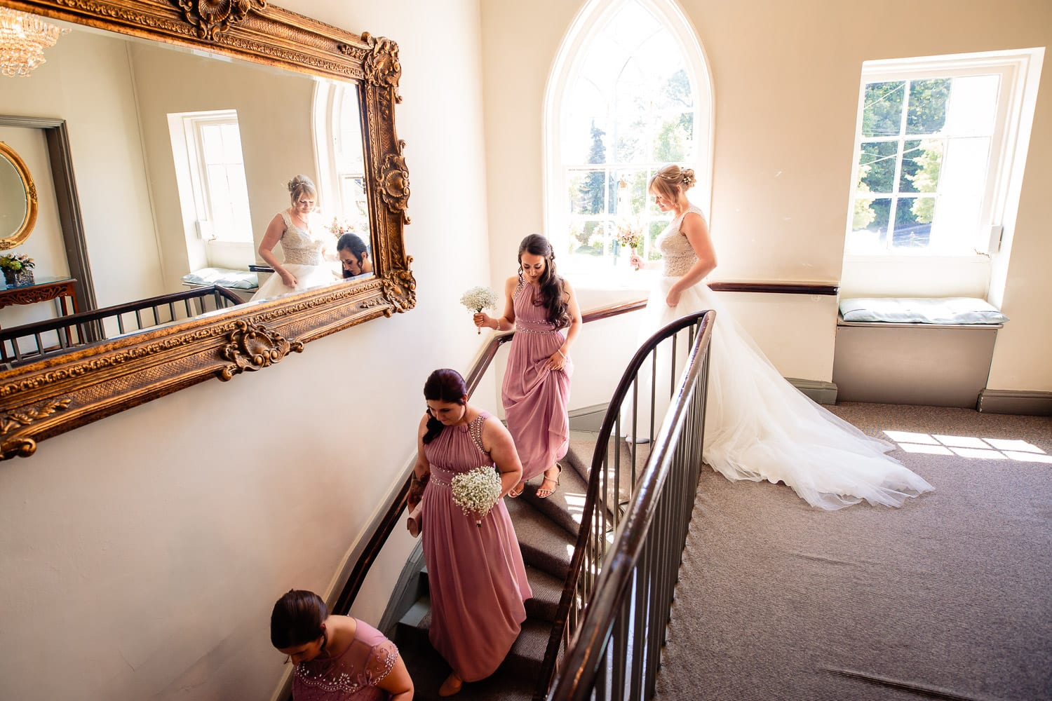 Warwick House Wedding Photography captures bridal party going down stairs to the ceremony room at Warwick House