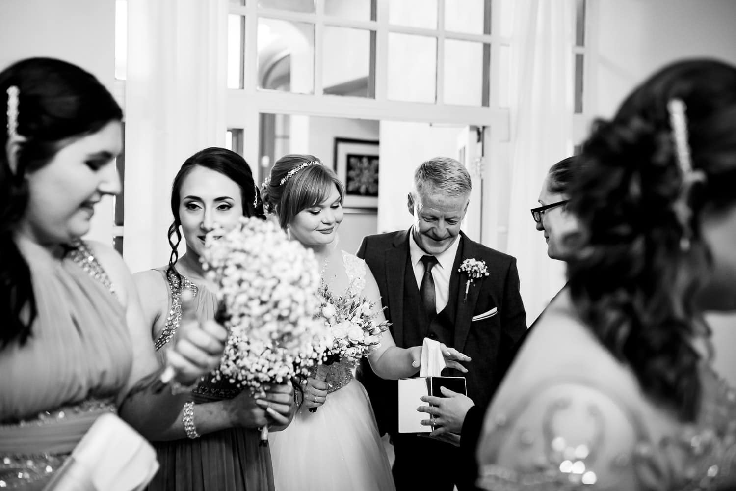 tearful bride reaching for a tissue captured by Warwick House Wedding Photography