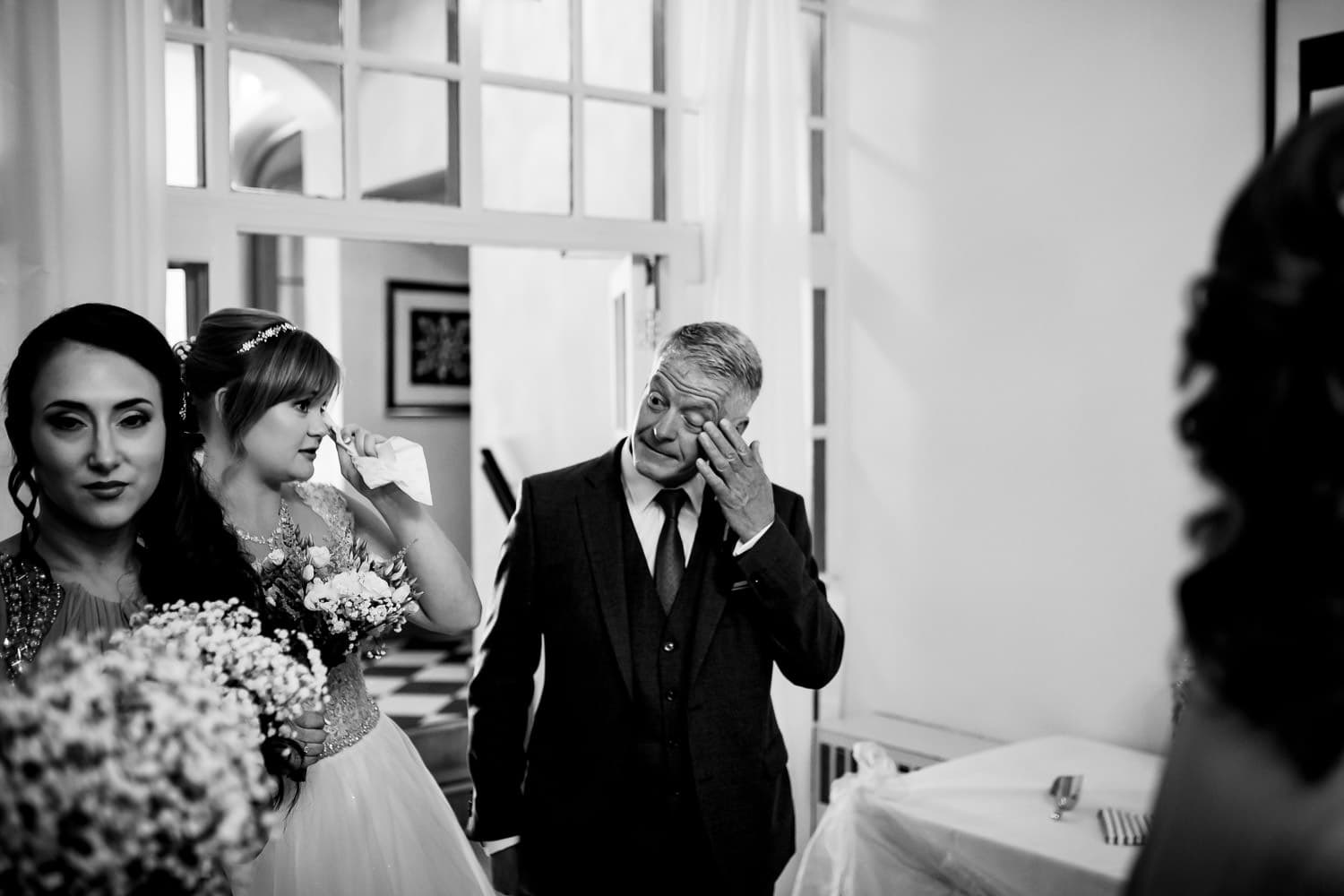 tearful and emotional dad wiping a tear from his eye captured by Warwick House Wedding Photography