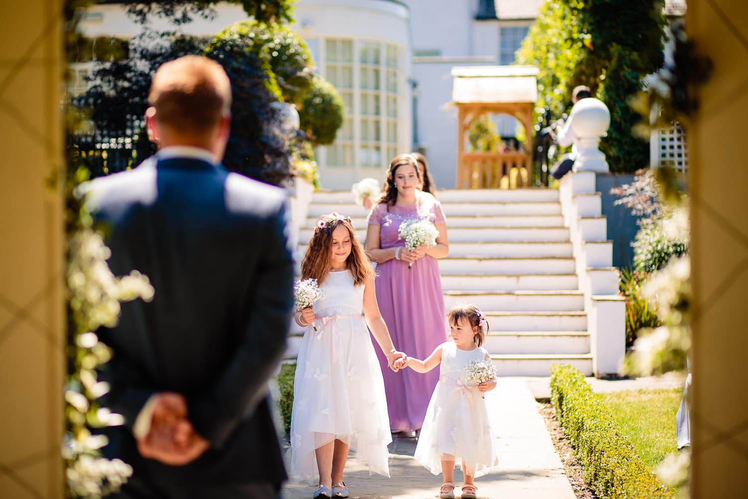 groom watches bridesmaids procession captured by Warwick House Wedding Photography