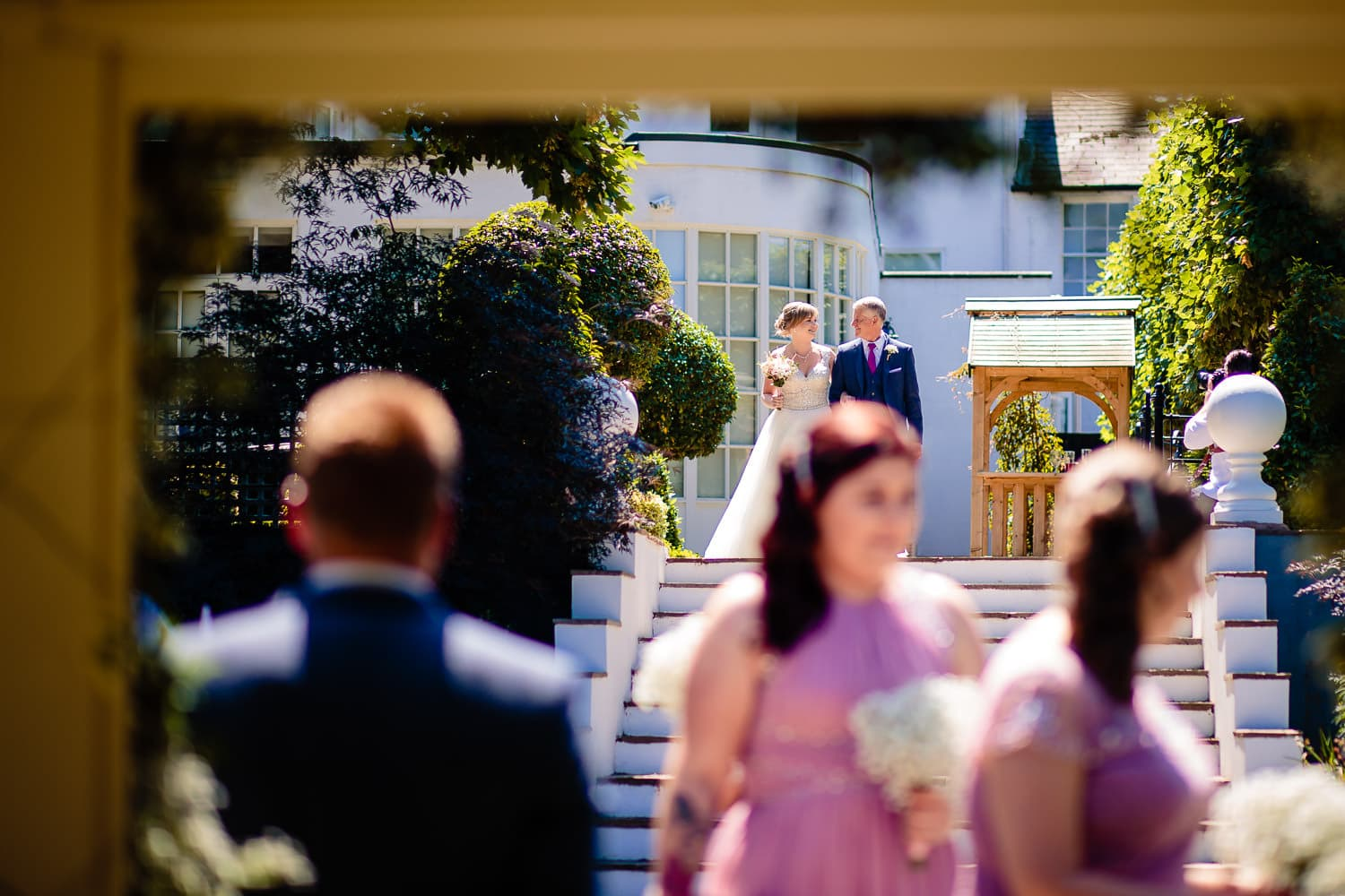 groom looks on while dad walks his daughter down the aisle by Warwick House Wedding Photography