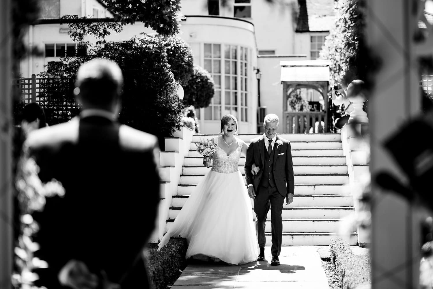Warwick House Wedding Photography captures dad and daughter laughing together whilst walking down the aisle
