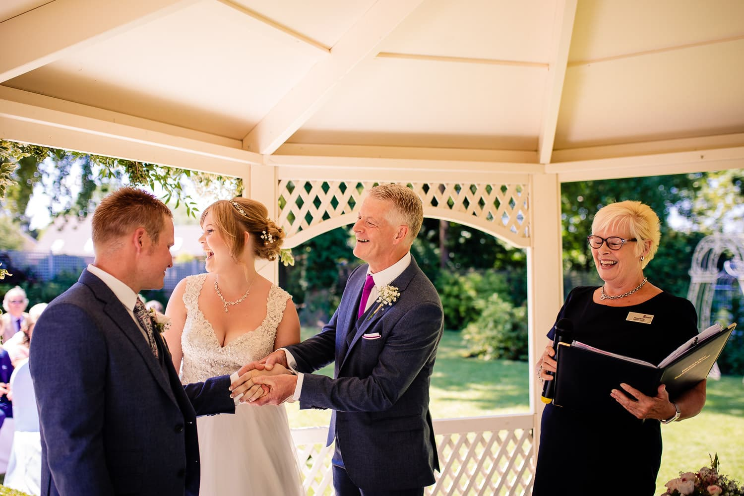 dad hands over daughters hand in marriage to smiling groom captured by Warwick House Wedding Photography