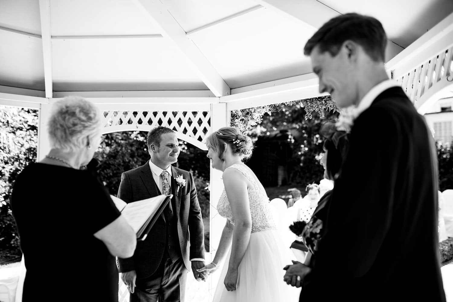 bride and groom laugh and share a joke during the ceremony captured by Warwick House Wedding Photography