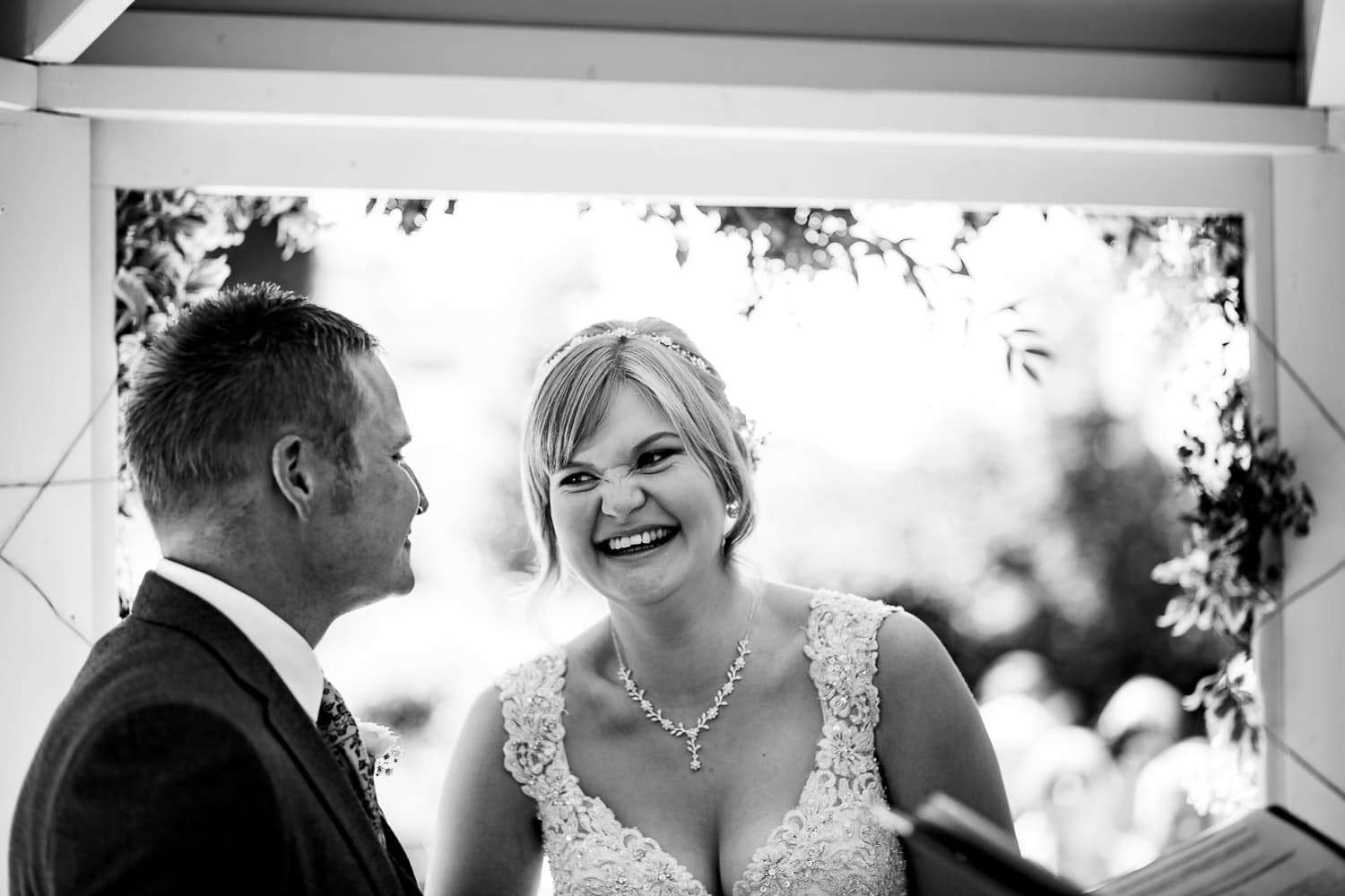 brides smiling at groom captured by Warwick House Wedding Photography