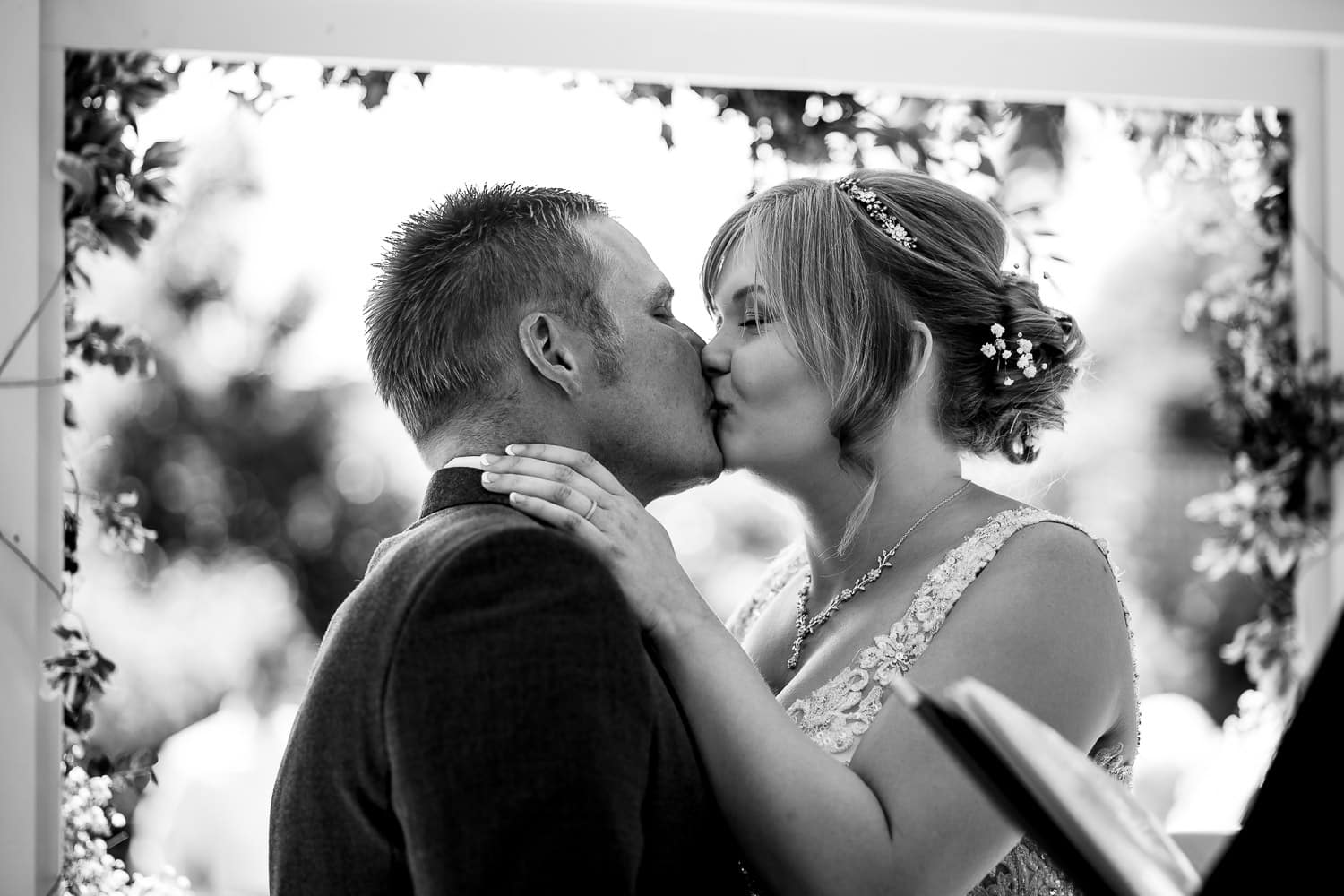 bride and groom sharing their first kiss as husband and wife captured by Warwick House Wedding Photography