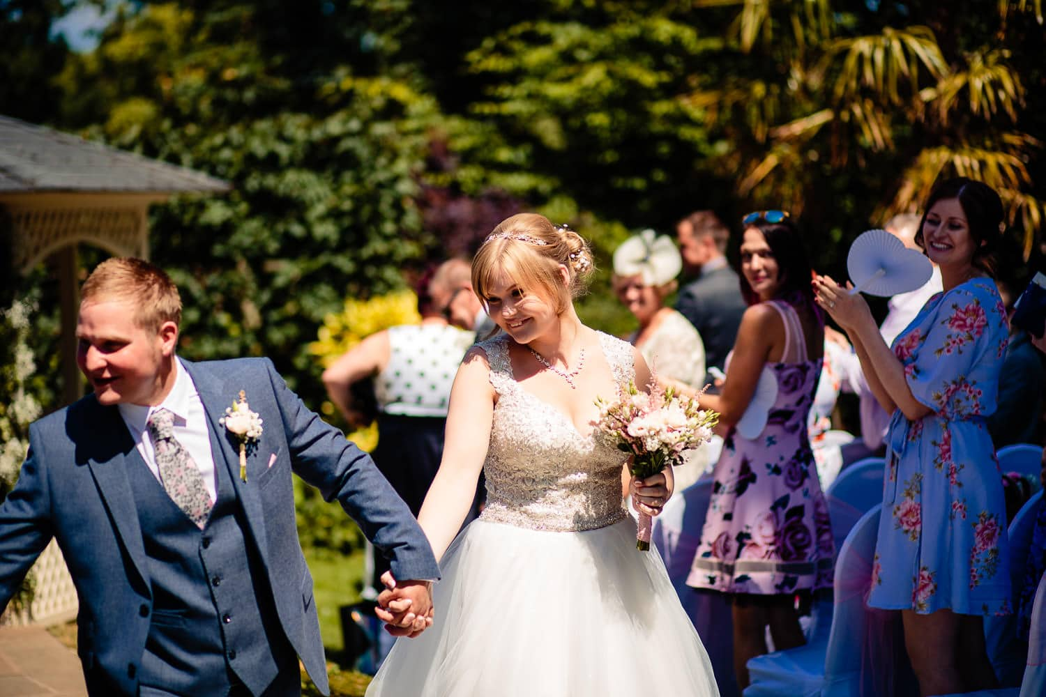 Warwick House Wedding Photography captures Warwickshire newlyweds walking down the aisle to applause of guests