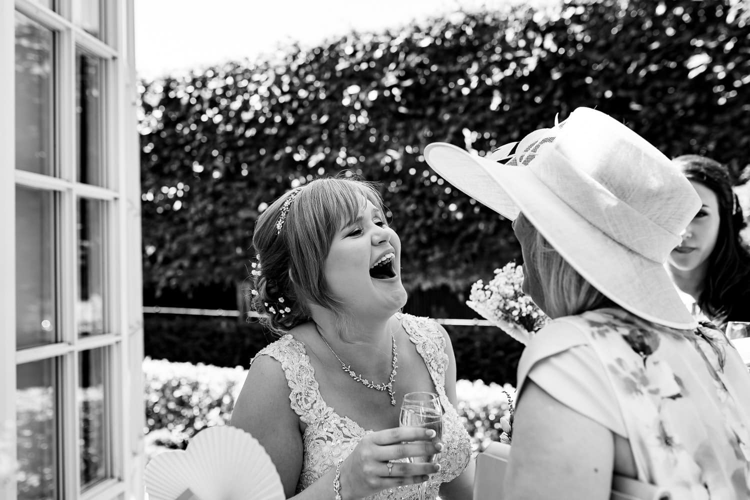 Candid picture of guests laughing with bride by Warwick House Wedding Photography