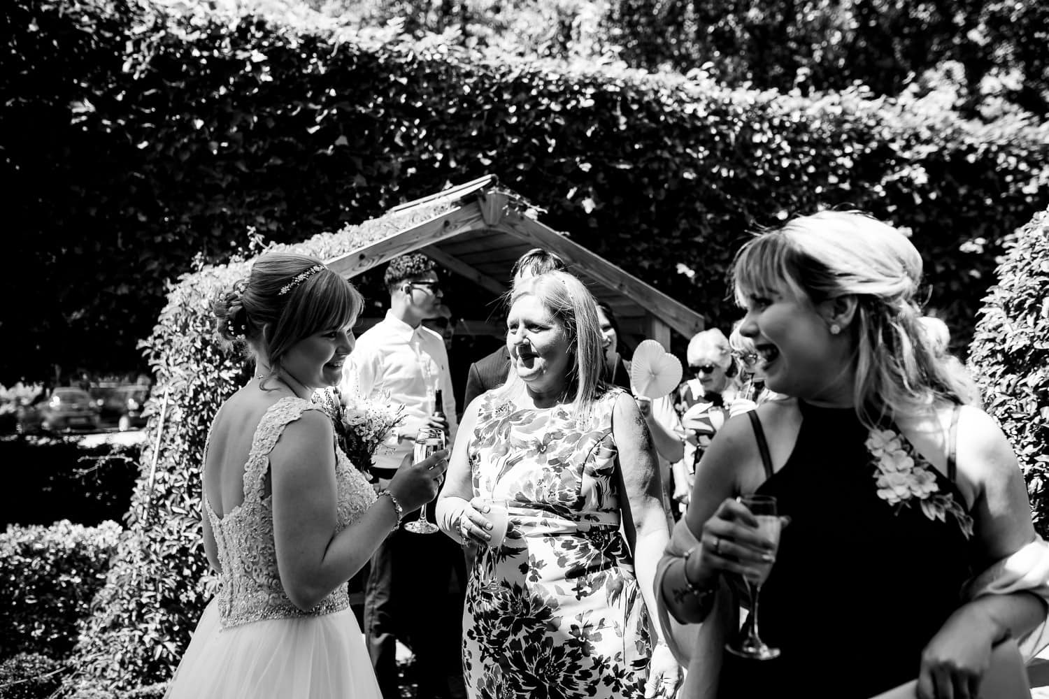 Guests laughing and sharing happy moments with the bride by Warwick House Wedding Photography