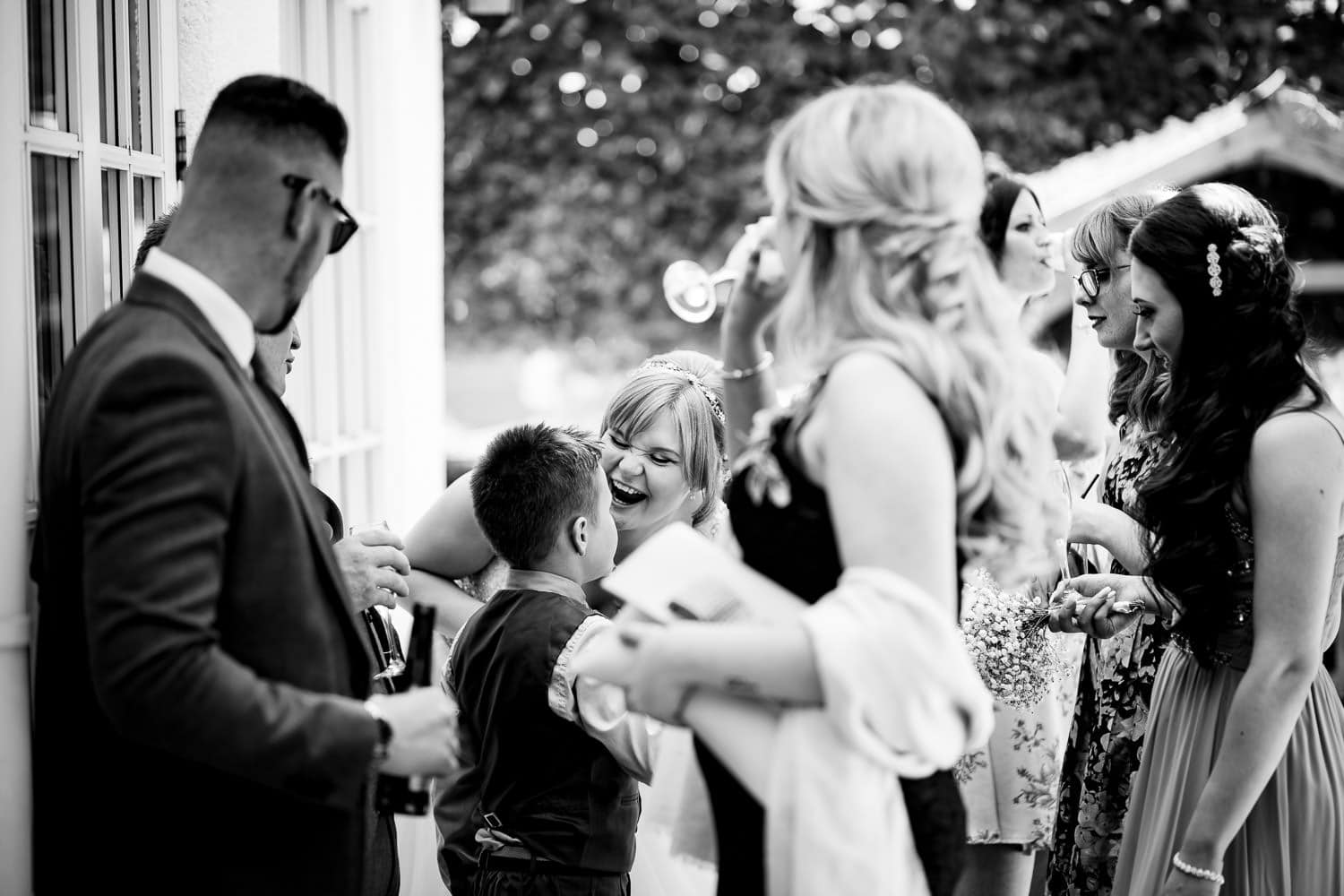 warwickshire wedding photographers capture bride laughing and joking with young boy
