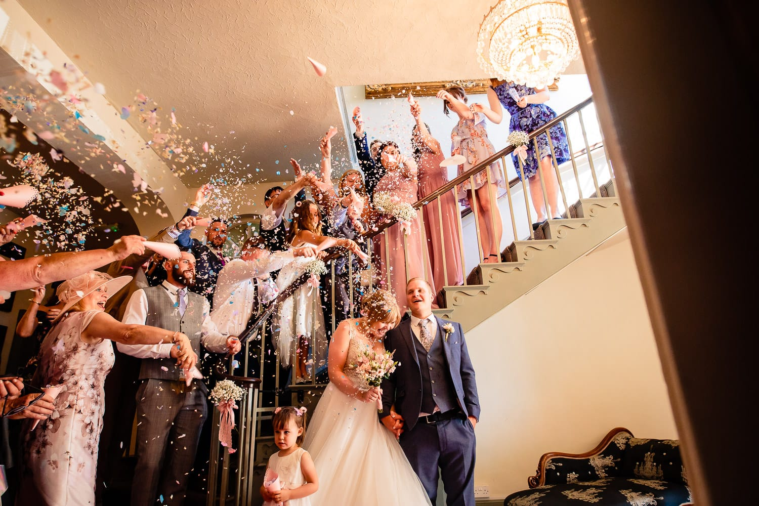 Warwick House Wedding Photography captures guests throwing confetti onto bride and groom