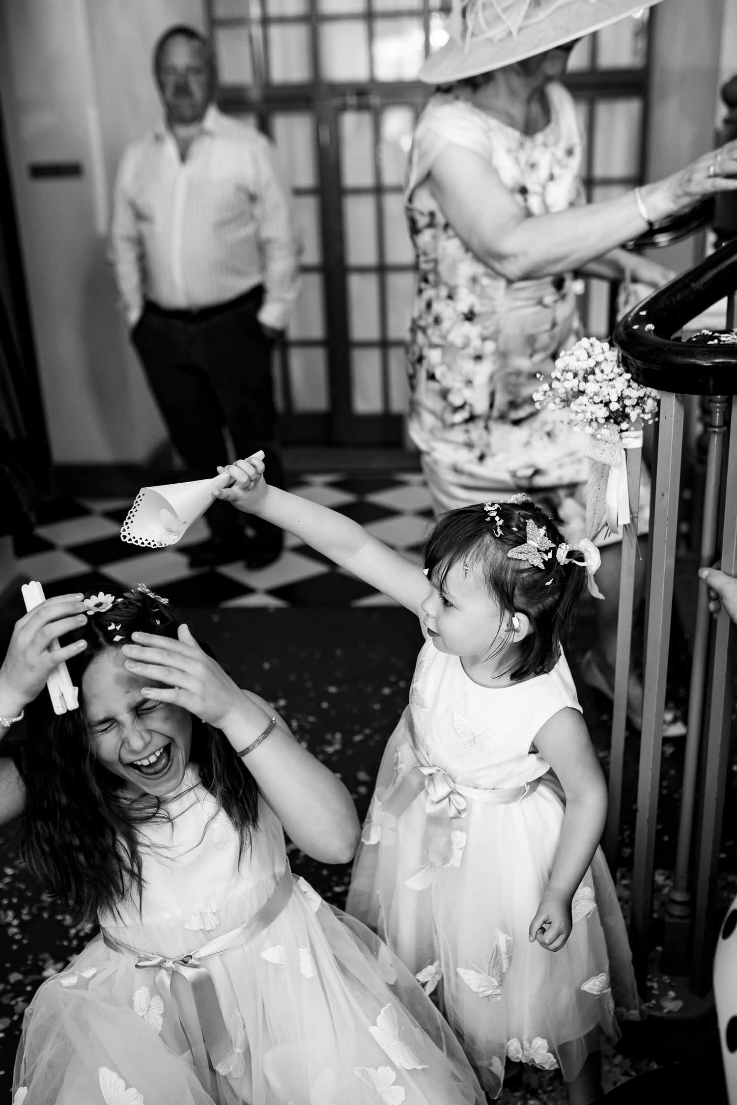 girls playing with confetti by Warwick House Wedding Photography