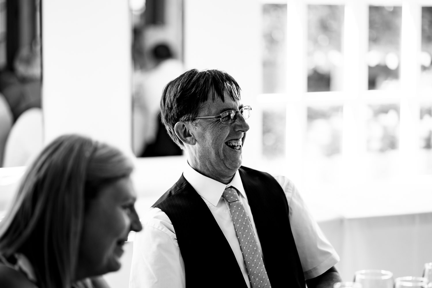 Man smiles during wedding speeches by Warwick House Wedding Photography