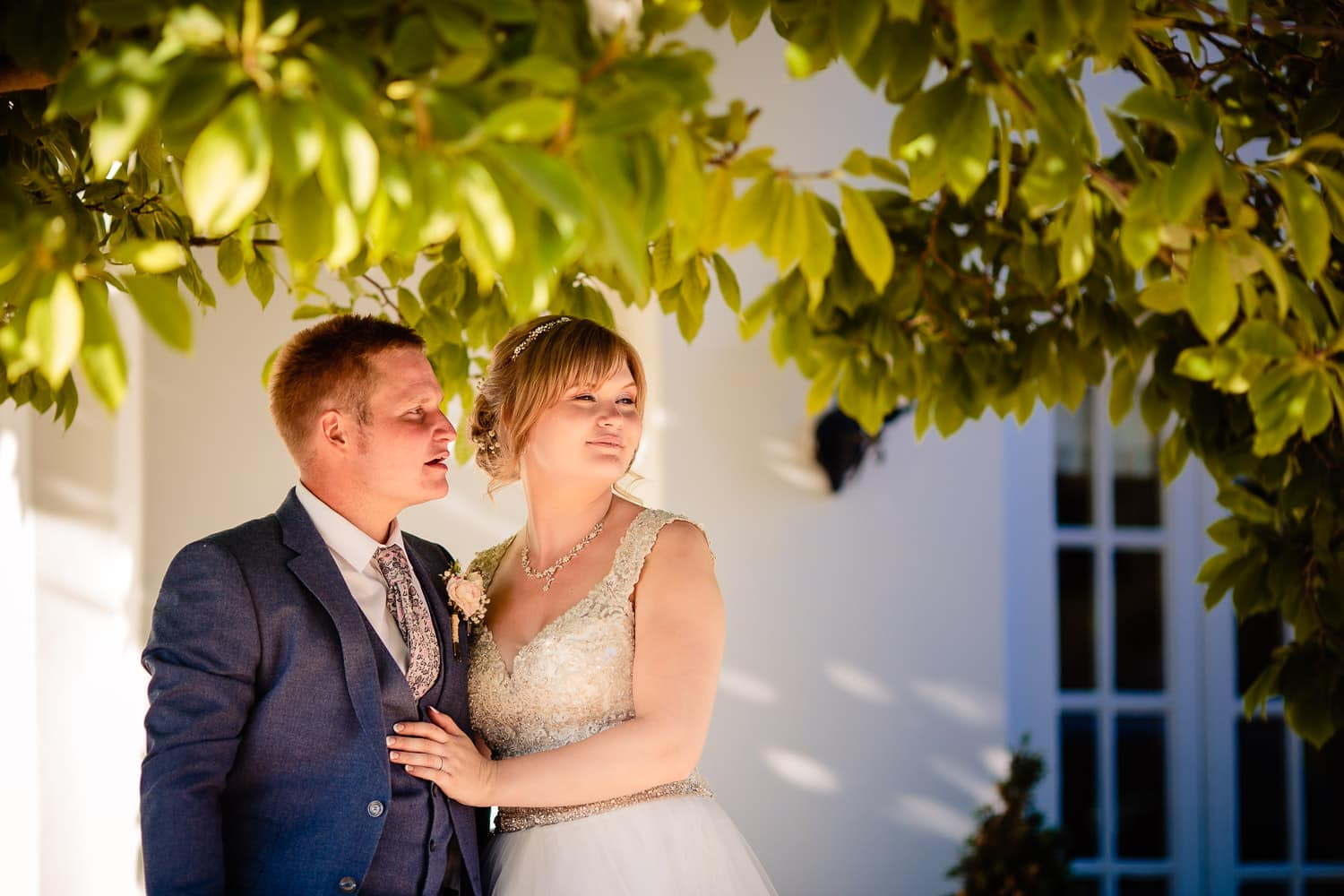beautiful bride and groom posing together under a tree by Warwick House Wedding Photography