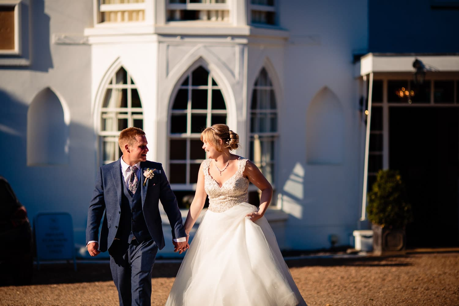 Warwick House Wedding Photography captures bride and groom walking in the sunshine and smiling to each other
