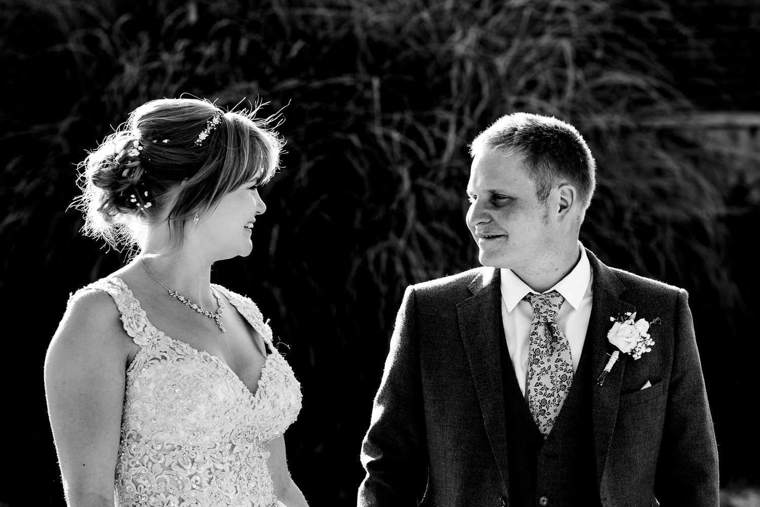 bride and groom smile looking and smiling at each other by Warwick House Wedding Photography