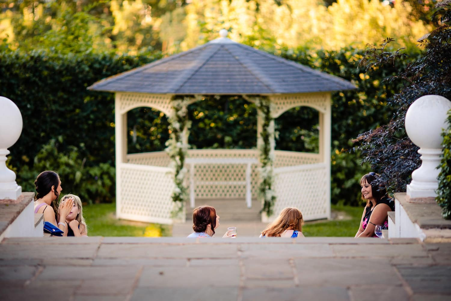 Bridal party relax on the steps at Warwick house in Southam after long wedding day by Warwick House Wedding Photography