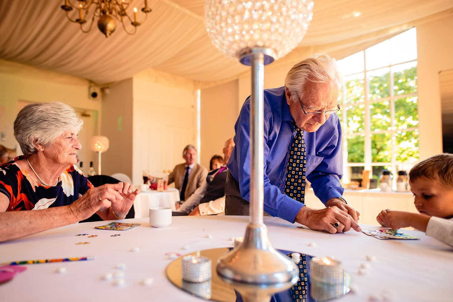 wedding guests build a puzzle during Warwick House wedding reception by Warwick House Wedding Photography