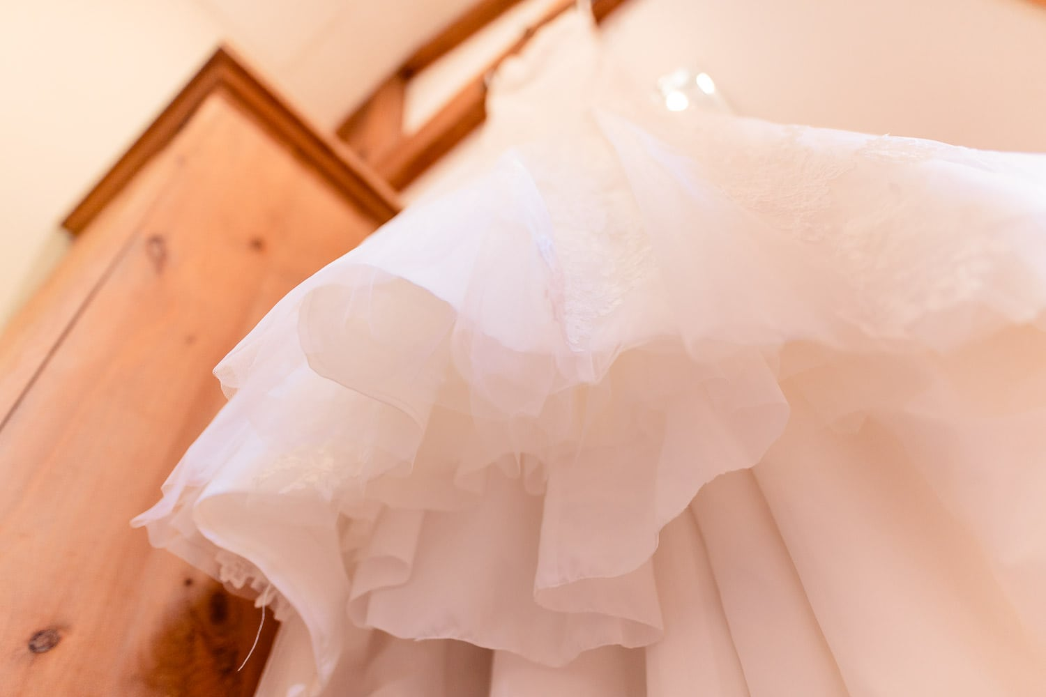 beautiful wedding dress hangs on the door frame at The Granary at Fawsley Wedding venue