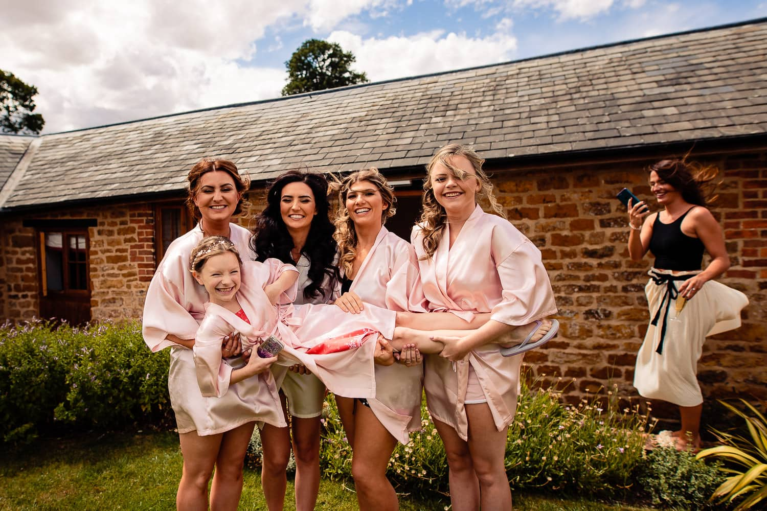 The Granary at Fawsley Wedding bridal party have fun in the courtyard