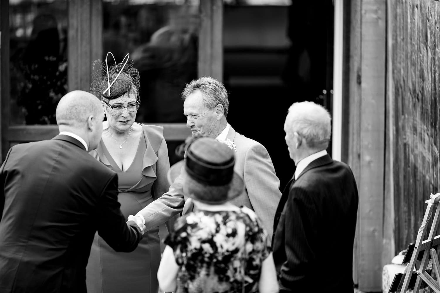 The Granary at Fawsley Wedding guests shake hands before the wedding ceremony in northamptonshire
