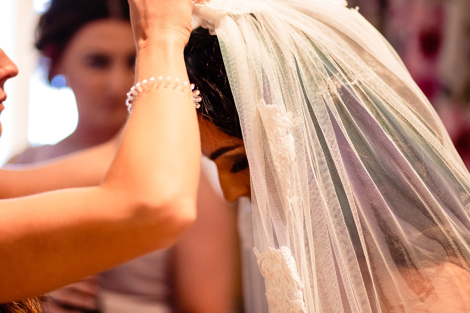bride putting on veil at the Granary at Fawsley Wedding by chapter one photography