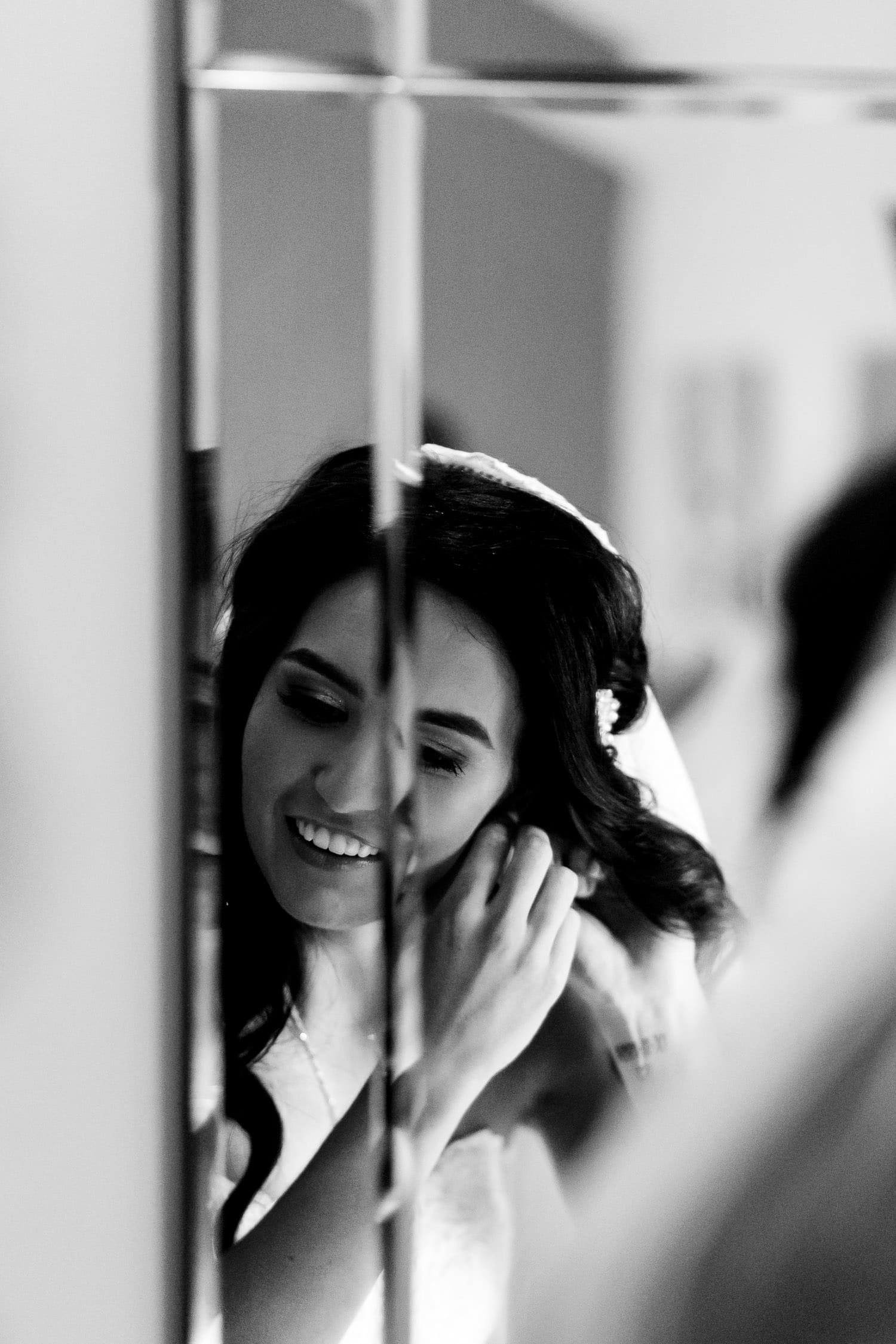 bride putting on her earrings at the Granary at Fawsley Wedding