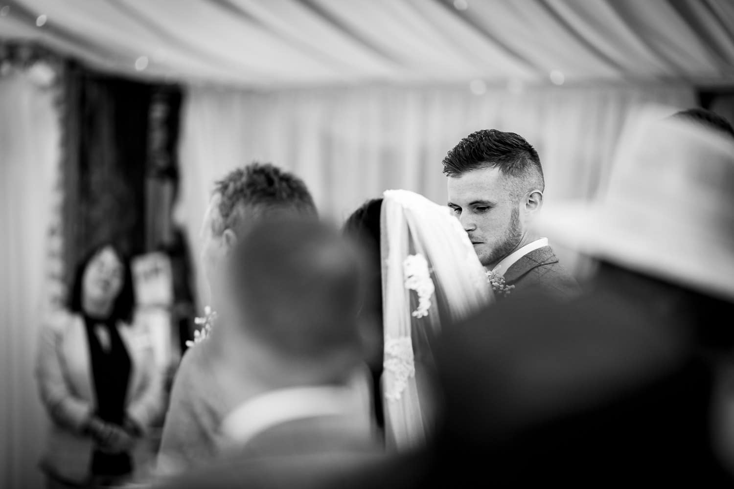 Groom looks lovingly at his bride during ceremony at The Granary at Fawsley Wedding barn in Northampton